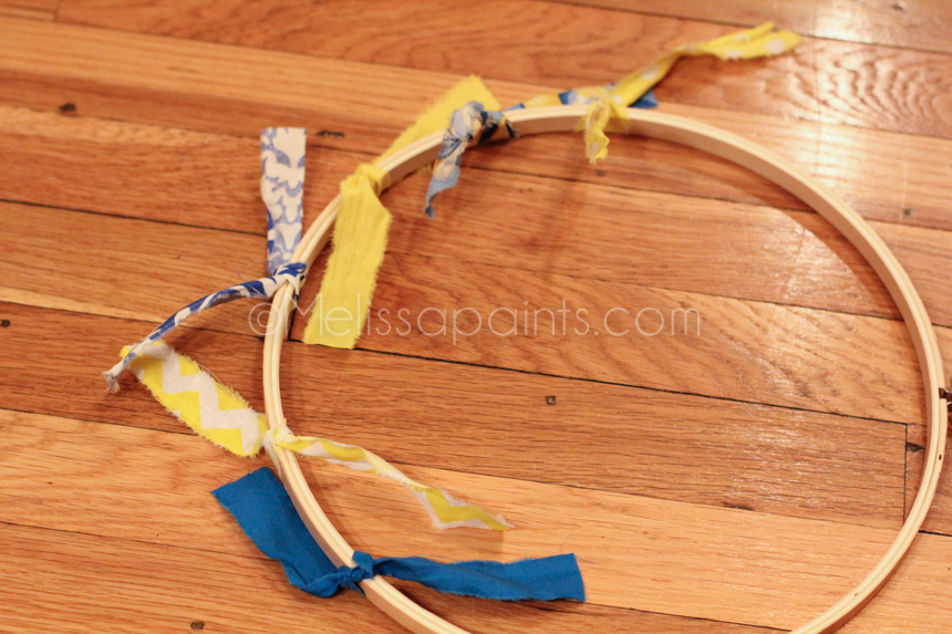Take a strip and tie the fabric on the embroidery hoop in a tight single knot.